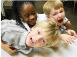 Young kids laughing as they are playing together in a childcare program