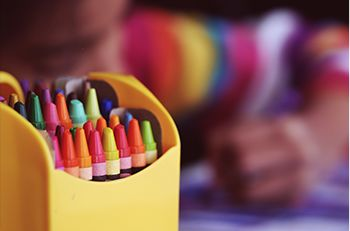 Box of crayons and children drawing pictures in background