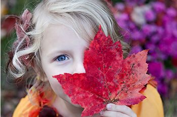 Young girl playing with leaf outside in the garden