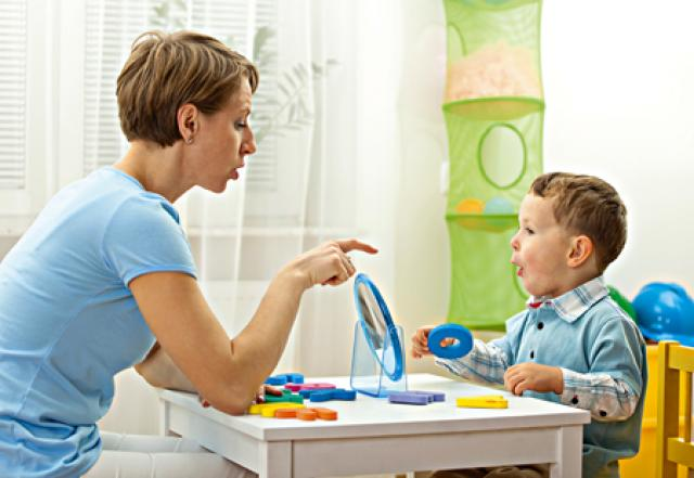 Teacher speech therapist with young child learning speech development